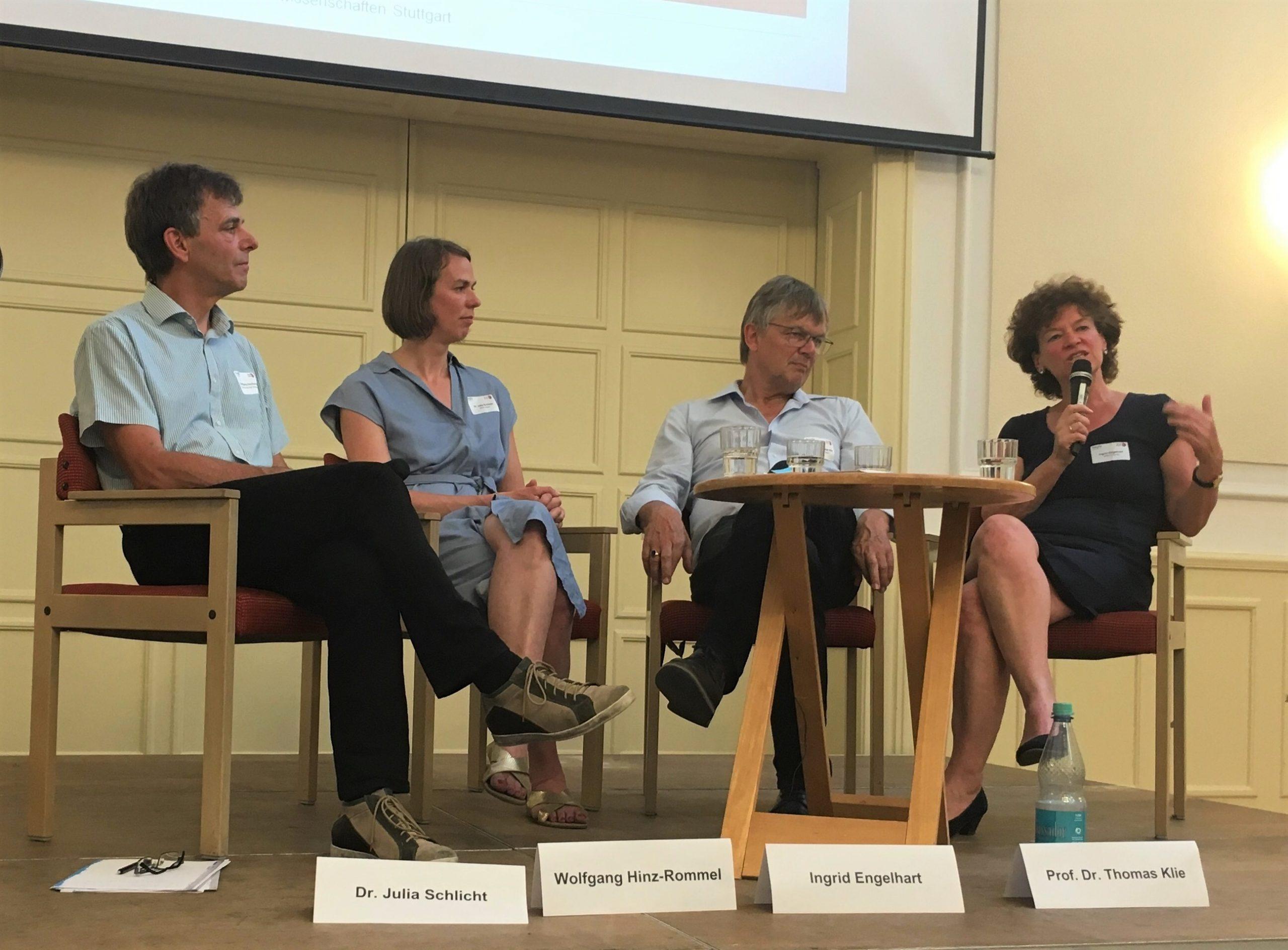 Vier Personen sitzen auf einer Bühne im Halbkreis um einen Beistelltisch. Die Frau auf der rechten Seite spricht in ein Mikrofon.