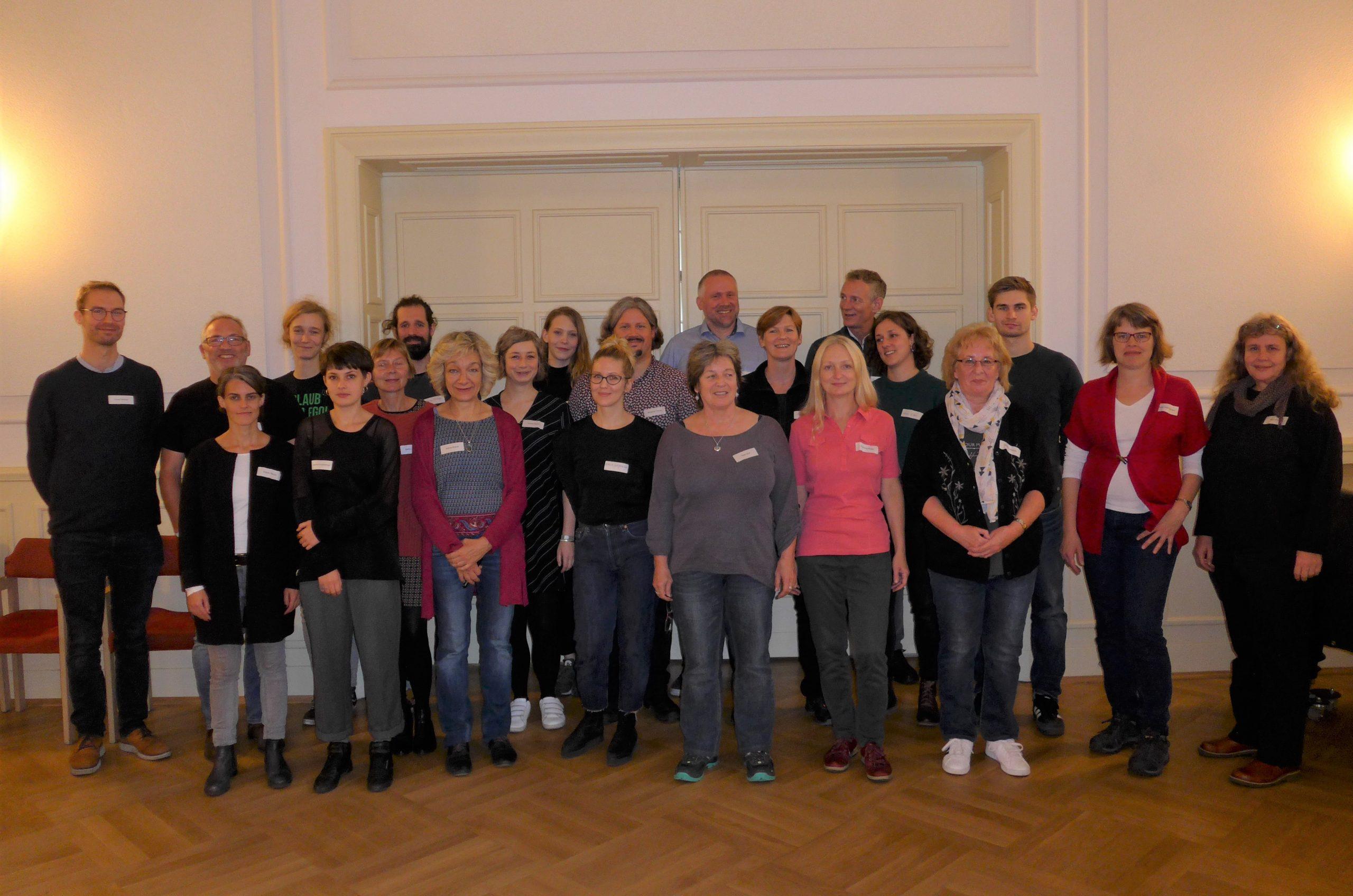 Gruppenfoto von 22 Personen im Saal des Nachbarschaftshaus Urbanstraße in Berlin.
