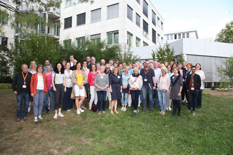 Gruppenfoto des Netzwerkpartnertreffens 2019 auf einer grünen Wiese. Im Hintergrund das Gebäude der Aktion Mensch in Bonn.