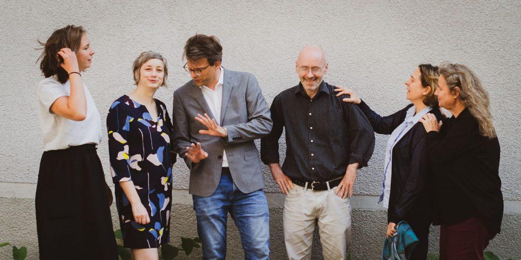 Die sechs aktuellen Mitarbeiter/innen der bagfa stehen fröhlich vor einer grauen Wand.