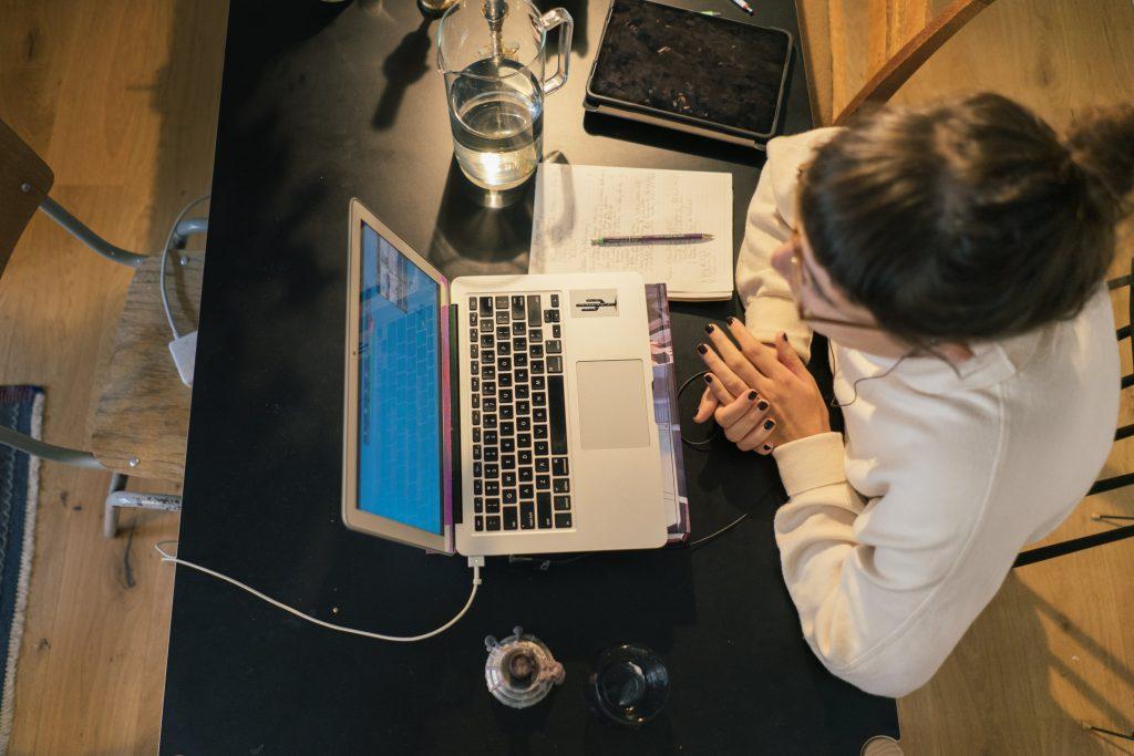 Draufsicht auf eine am Tisch sitzende Frau mit Laptop
