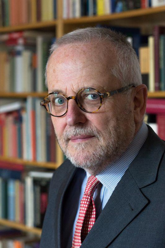 Portrait von Rupert Graf Strachwitz vor einer Bücherwand