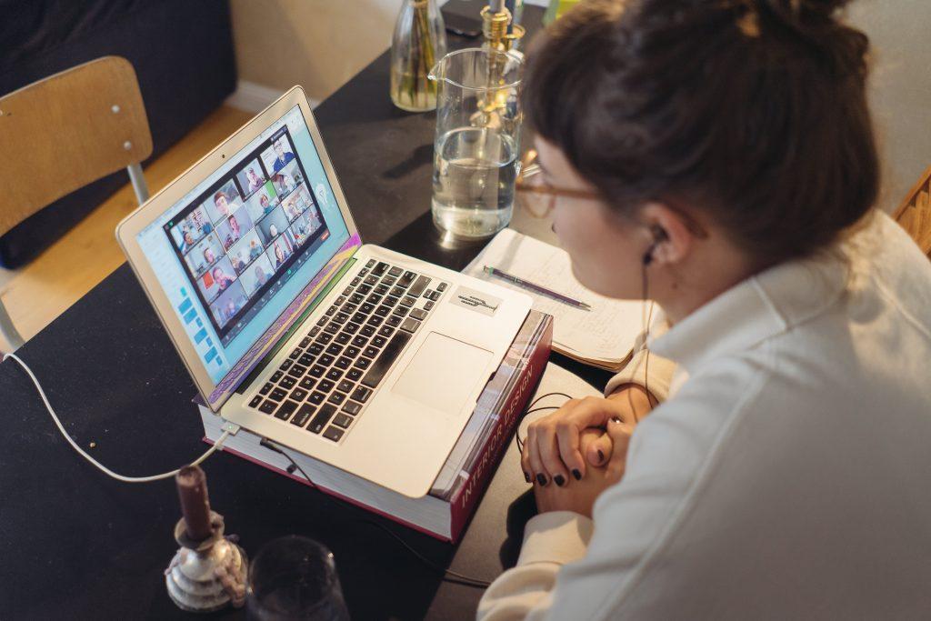 Frau sitzt am Laptop und schaut auf eine Zoom Konferenz
