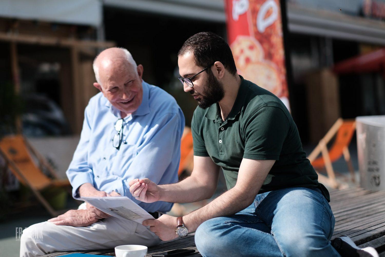 Ein älterer und ein jüngerer Mann sitzen auf einer Bank und schauen gemeinsam auf ein Papier.