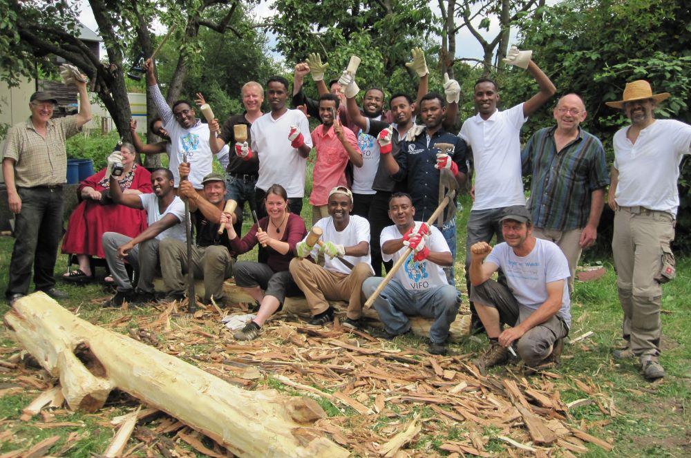Eine Gruppe von Menschen winkt fröhlich in die Kamera, im Vordergrund ein großer Baumstamm