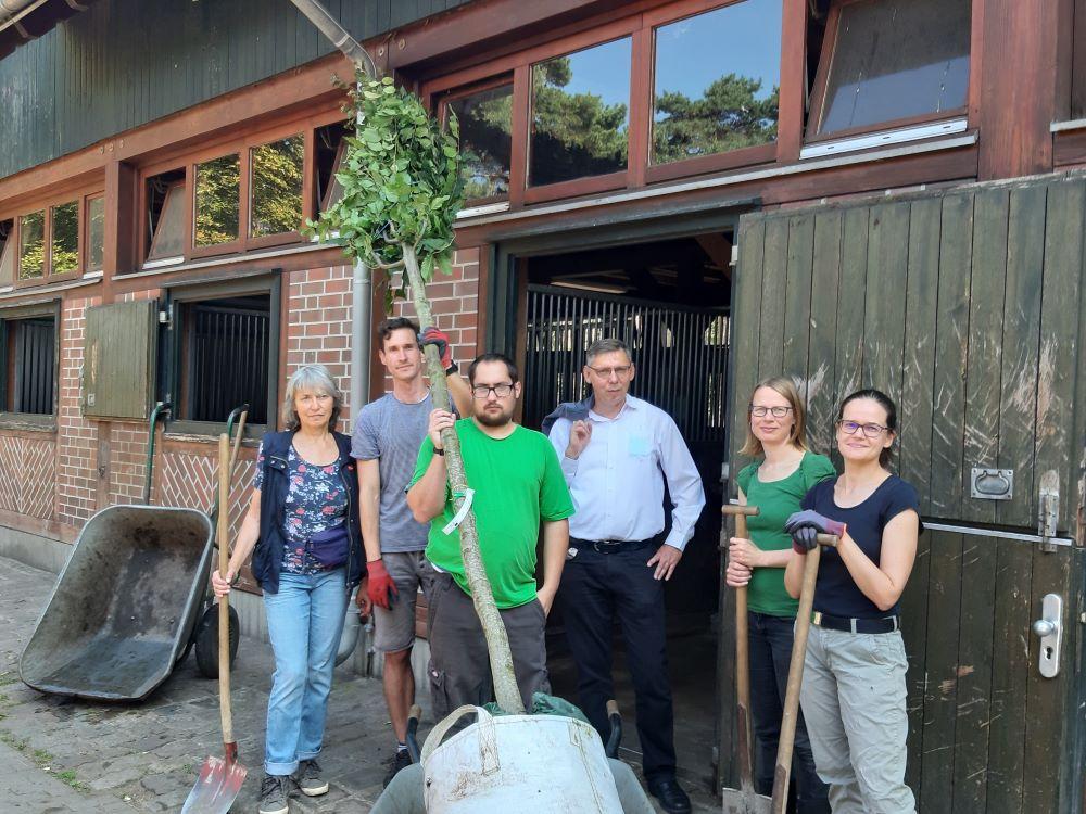 Sechs Personen vor einem Stallgebäude, mit Spaten und einem jungen Baum zum einpflanzen